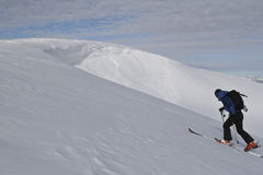 De skiër beklimt de heuvel. Stock Foto
