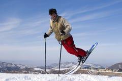 De Skiër die van de sneeuw over Blauwe Hemel springt stock fotografie