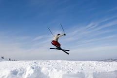 De Skiër die van de sneeuw tegen Blauwe Hemel springt stock foto's