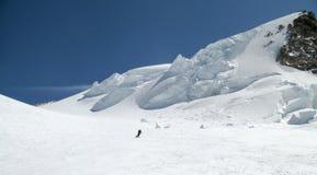 De skiër die van het binnenland onderaan een reusachtige alpiene gletsjer op een mooie de winterdag ski?en met het hangen van ijs royalty-vrije stock fotografie