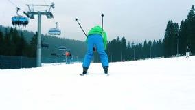 De skiër gaat bergaf voorbijgaand de camera liggend in sneeuw stock video