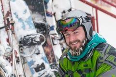 De skiër in het masker op het gezicht van een sneeuwmens en een sneeuw ski?t stock afbeelding