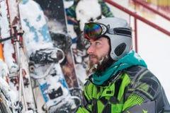 De skiër in het masker op het gezicht van een sneeuwmens en een sneeuw ski?t stock fotografie