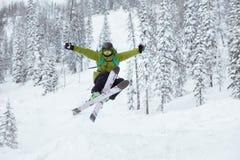 De skiër springt offpiste toevlucht van de skihelling stock foto