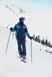 De skiër van de mens in skikostuum bevindt zich neer kijkend Stock Foto's