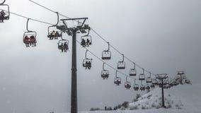 De skiërs berijden op een skilift in bewolkt weer in de sneeuwval 4K timelapse Januari 2017, Kazachstan stock footage