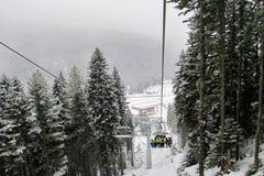 De skiërs en snowboarders beklimmen op de helling op een zes -zes-seater stoellift in het snow-covered bos royalty-vrije stock afbeeldingen