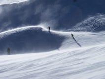 De skiërs in geveegde wind ski?en piste Stock Afbeelding