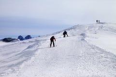De skiërs op ski hellen bij winddag Stock Afbeelding