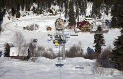 De skiërs op stoeltjeslift bij ski nemen in de dag van de zonwinter zijn toevlucht Stock Foto