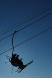 De skiërs silhouetteren op kabelbaan Stock Afbeelding