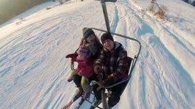 De skiërsfamilie die omhoog bij de skilift berijden en maakt selfie stock videobeelden