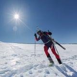 De skibergbeklimmer reduceert de berghelling met skis aan rugzak worden vastgebonden die Royalty-vrije Stock Foto's