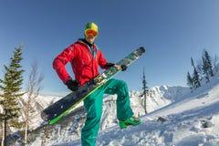 De skibeschermende brillen die van de portret jonge mens ski in de bergen houden Royalty-vrije Stock Afbeeldingen