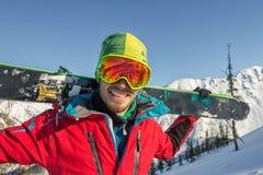 De skibeschermende brillen die van de portret jonge mens ski in de bergen houden Stock Foto