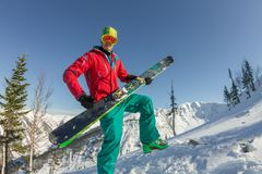 De skibeschermende brillen die van de portret jonge mens ski in de bergen houden Stock Afbeeldingen
