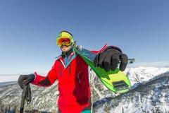 De skibeschermende brillen die van de portret jonge mens ski in de bergen houden Royalty-vrije Stock Afbeelding