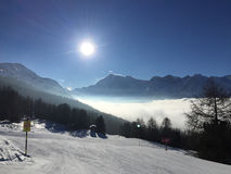 De skihellingen van de de winterscène Zon en wolken over sneeuw behandelde bergen Royalty-vrije Stock Foto