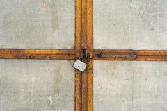 De skrapade gamla hänglåsslutgrå färgerna belägger med metall dörren eller porten, abstrakt bakgrund Arkivbild