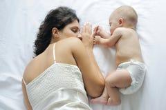 De slaap van de baby dicht bij haar moeder Stock Afbeeldingen