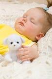 De slaap van de baby met haar beerstuk speelgoed Stock Afbeeldingen