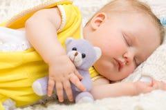 De slaap van de baby met haar beerstuk speelgoed Stock Foto's
