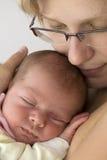 De slaap van de baby in moederswapen Stock Afbeelding