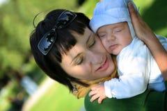 De slaap van de baby op de wapens van de moeder Stock Afbeelding