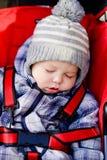 De slaap van de babyjongen in de wandelwagen Stock Foto