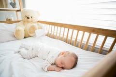 De slaap van de babyjongen op een wieg stock afbeelding