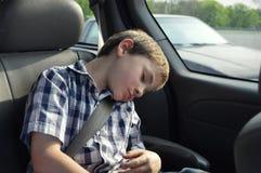 De slaap van de jongen in auto stock afbeelding
