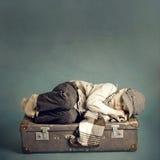 De slaap van de jongen op een koffer stock afbeeldingen