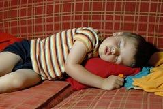 De slaap van de jongen op een rode bank Royalty-vrije Stock Foto's