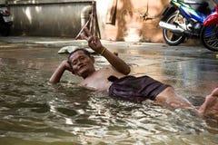 De slaap van de mens op de straat tijdens vloed Royalty-vrije Stock Foto
