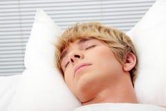 De slaap van de mens in zijn bed Royalty-vrije Stock Foto's