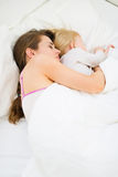 De slaap van de moeder en van het jonge geitje samen in bed Stock Afbeelding