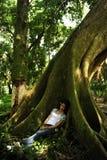 De slaap van de vrouw in de schaduw van een boom Stock Foto's