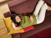 De slaap van de vrouw op bank stock fotografie