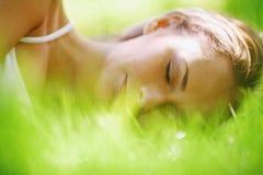 De slaap van de vrouw op gras Stock Afbeeldingen