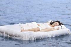 De slaap van de vrouw op het bed in het overzees Stock Afbeelding