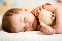 De slaap van de zuigelingsbaby met pluchestuk speelgoed Stock Afbeelding