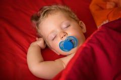De slaap van de zuigelingsjongen met soother royalty-vrije stock foto's
