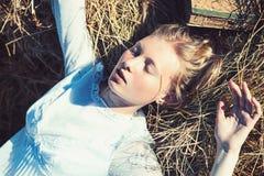 De slaap van het albinomeisje op hooi Vrouw met natuurlijke blik en geen make-up Sensuele vrouw met lang blond haar Schoonheidsmo stock afbeelding