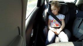 De slaap van het babymeisje in de auto op de manier Slaapkind bij achterstoel in auto stock videobeelden