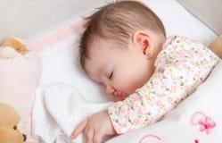 De slaap van het babymeisje in een wieg met fopspeen en stuk speelgoed Stock Fotografie