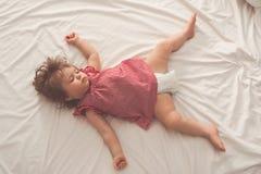 De slaap van het babymeisje op terug met open wapens en zonder fopspeen in een bed met witte bladen Vreedzame slaap in helder stock foto's