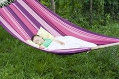 De slaap van het babymeisje in tuin Stock Foto's