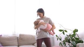 De slaap van het babymeisje in wapens van moeder stock video