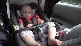 De slaap van het babymeisje in de zetel van de kindauto stock video