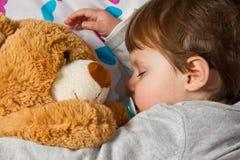 De slaap van het kind met teddybeer Royalty-vrije Stock Afbeeldingen